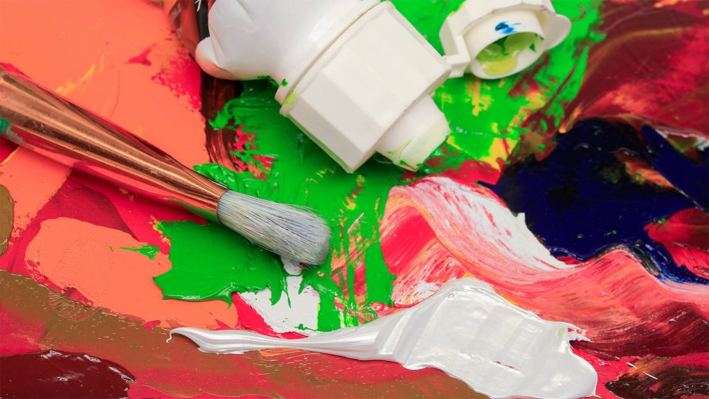 a variety of paints on paper next to a tube and a brush