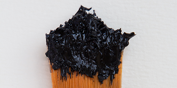 black paint on the end of a paint brush