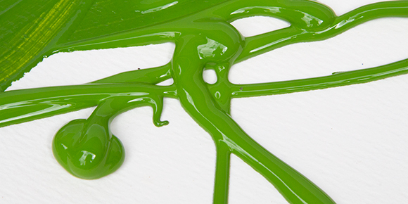 green liquid acrylic paint poured over paper