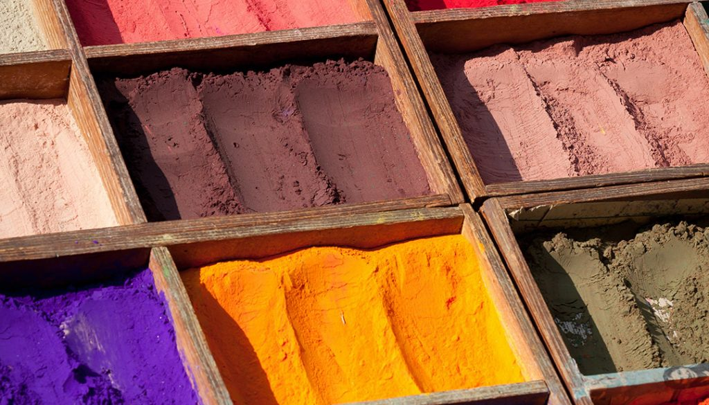 a row of boxes containing pigments in their raw form