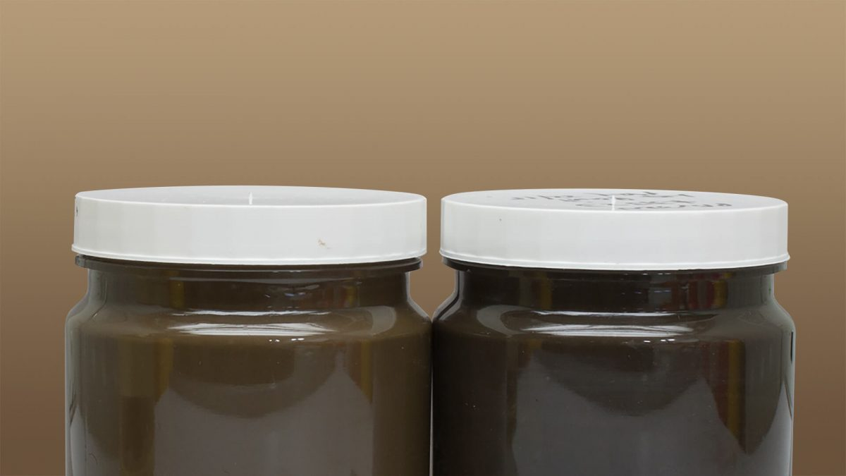 two brown paints side by side in jars to show improvement in mass tone