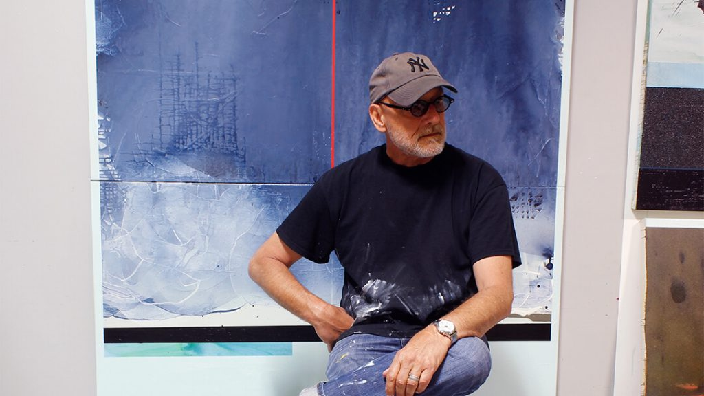 artist drew harris sitting on a stool in-front of his paintings
