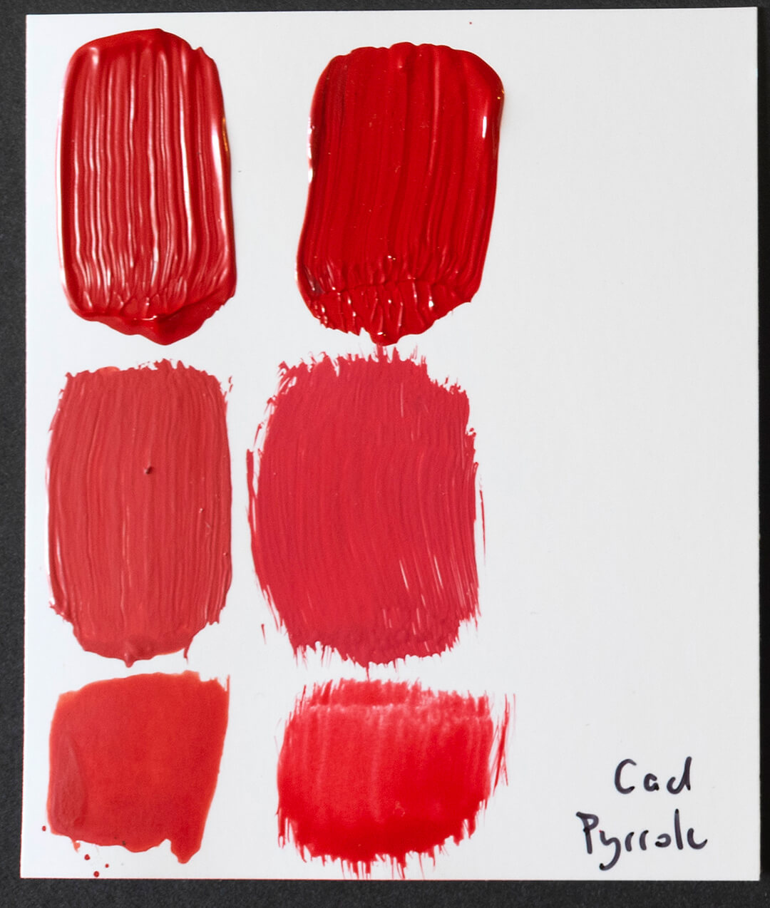 cadmium red swatches next to pyrrole red swatches