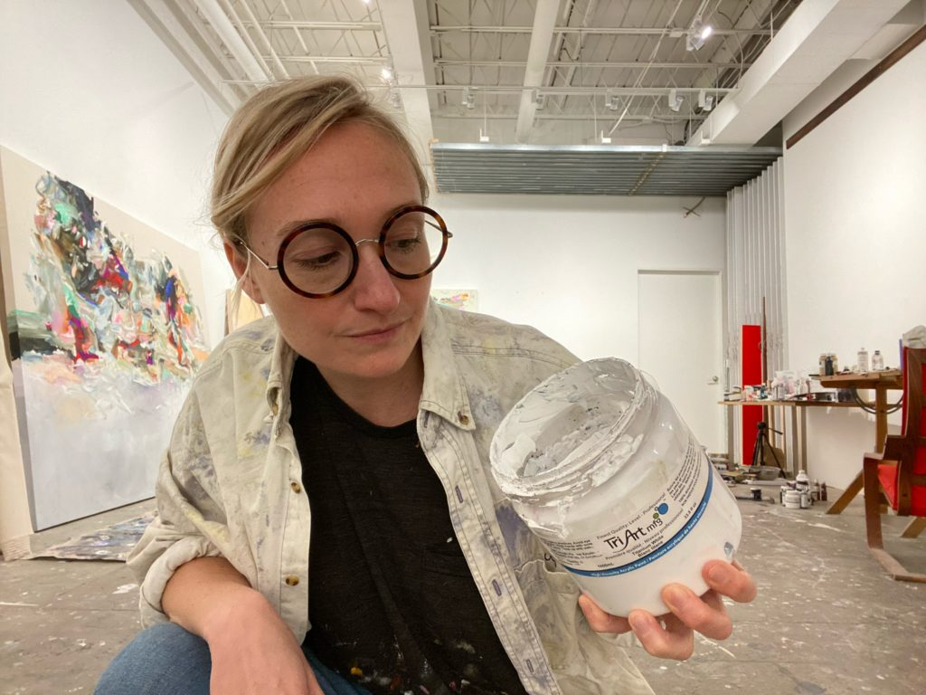 Janna Watson crouches in her studio, looking at a jar of well-used jar of High Viscosity Titanium White