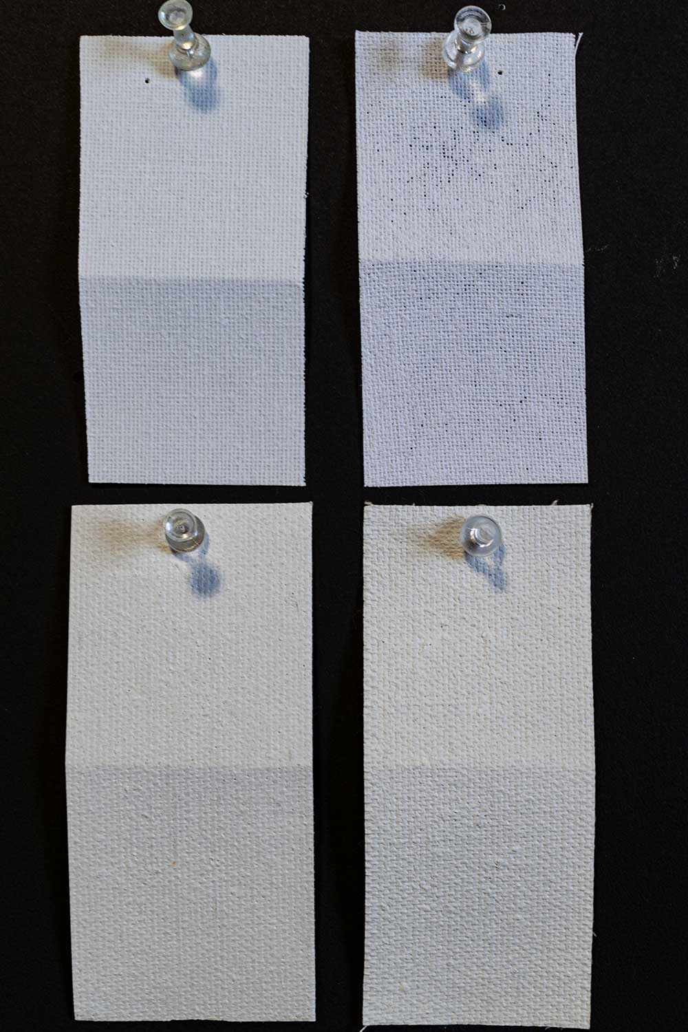 four canvas swatches from a water washing test. the discount store swatch shows less primer and pinholes after washing, the tri-art one shows negligible change.